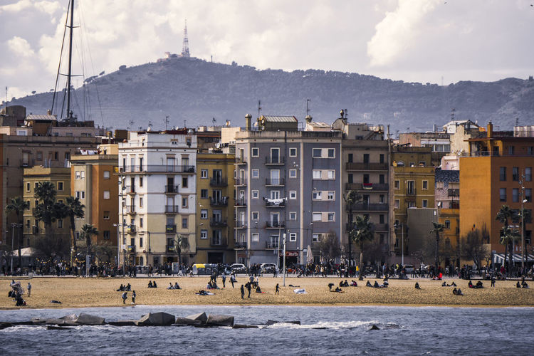 People enjoying the beach on a warm day SPAIN Barcelona Barcelona, Spain Ocean Coastline City Cityscape Politics And Government Photograph Low Residential Building Community Business Finance And Industry Abstract Town Sandy Beach Calm Shore