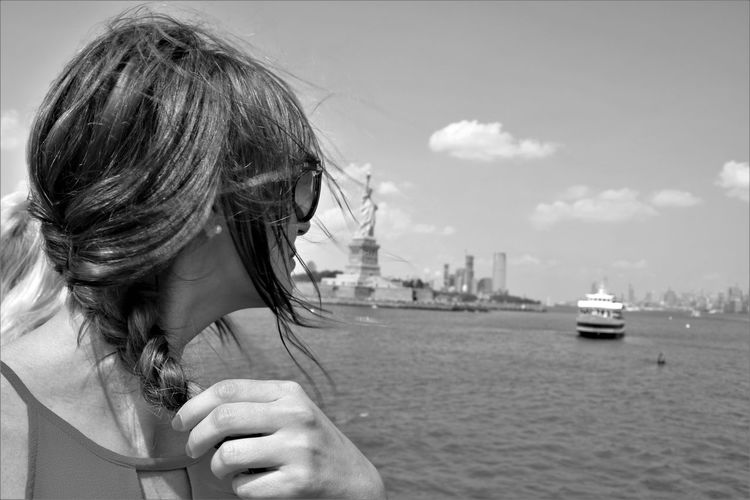 Mid adult woman looking at statue of liberty by river against sky