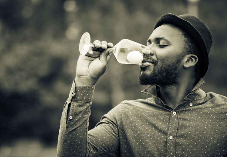 Portrait of young man drinking glass outdoors