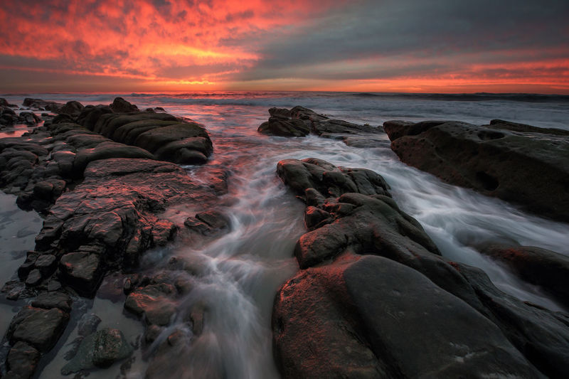 A beautiful sunset captured at Windansea Beach in La Jolla, California. Water Sea Rock Solid Rock - Object Sky Motion Sunset Scenics - Nature Beauty In Nature Long Exposure Cloud - Sky Horizon Over Water Blurred Motion Horizon Land Nature Orange Color Beach No People Outdoors Flowing Water Flowing Seascape Landscape