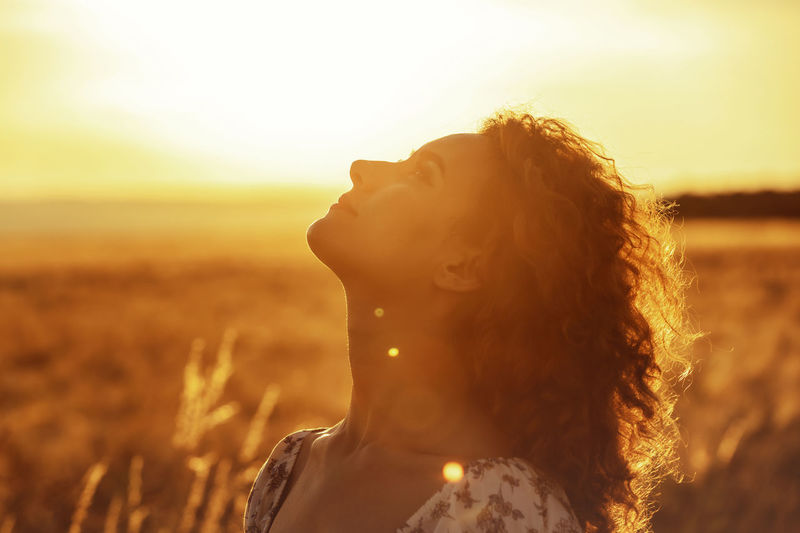 Portrait of woman looking away on field during sunset