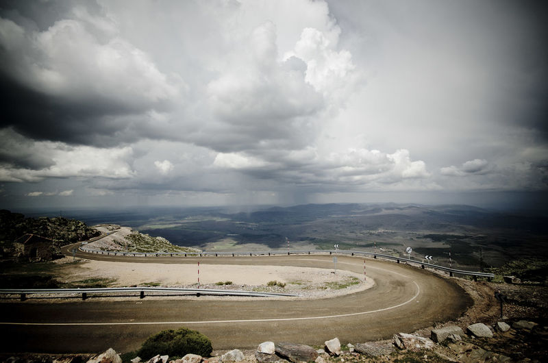 Empty Curved Road On Landscape Against Cloudy Sky