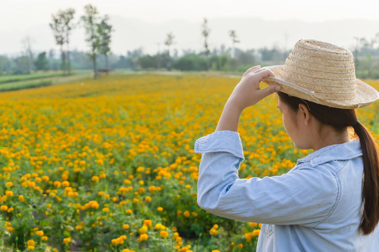 Marigold Portrait Flower Marigold Flower Farmer Selective Focus Lifestyles Outdoors Nature Plant Leisure Activity Care Check One Person Hat Real People Clothing Field Growth Yellow Land Beauty In Nature Waist Up Adult Women Rural Scene Focus On Foreground Agriculture Landscape Sun Hat Hairstyle