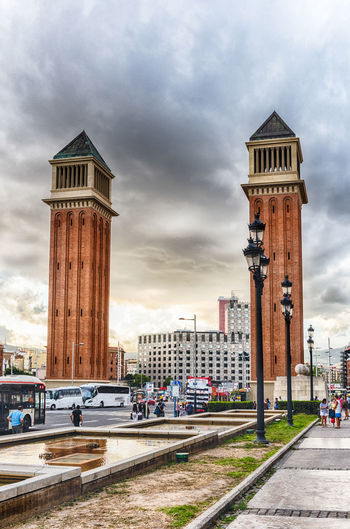 BARCELONA - AUGUST 11: Venetian Towers on Avinguda de la Reina Maria Christina, Barcelona, Catalonia, Spain, on August 11, 2017. The towers are modeled on Bell Tower of St. Mark Basilica in Venice Built Structure Architecture Building Exterior Sky Cloud - Sky Tower Building City Nature Transportation Incidental People Street Travel Destinations Travel Mode Of Transportation Day Outdoors Tall - High Motor Vehicle Tourism Architectural Column Office Building Exterior Skyscraper