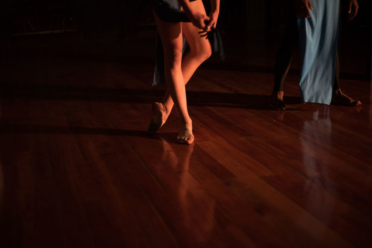 Low section of woman dancing on hardwood floor