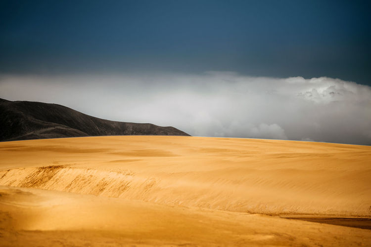 Sand dune contrasted by sky and dark mountain