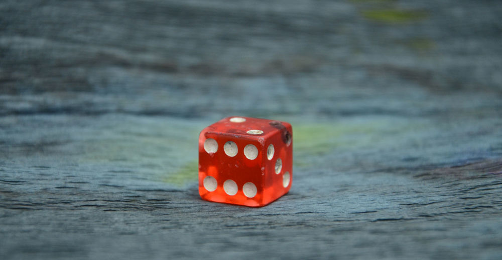 Close-Up Of Red Dice On Wooden Table
