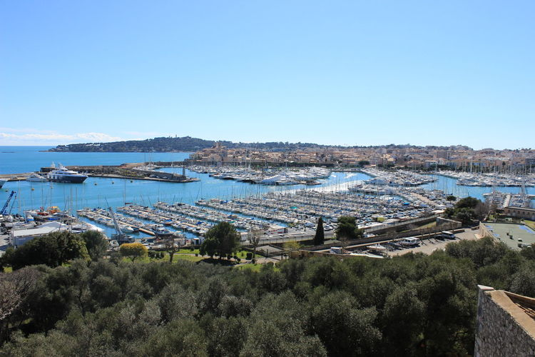 Panoramic view of sea and city against clear blue sky