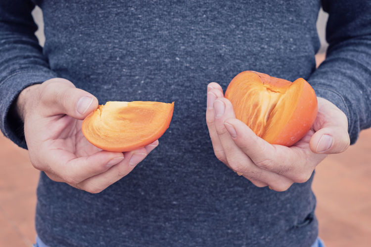 Midsection of man holding persimmon