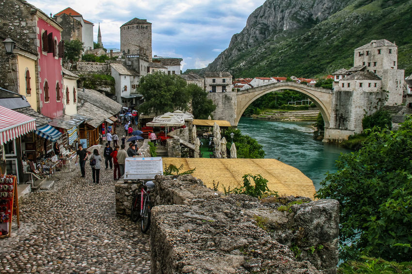 Mostar Mostar Bosnia Mostar Bridge Architecture Bridge - Man Made Structure Building Exterior Built Structure Cloud - Sky Connection Day Large Group Of People Men Mountain Nature Neretva River Outdoors People Real People Sky Transportation Tree Water