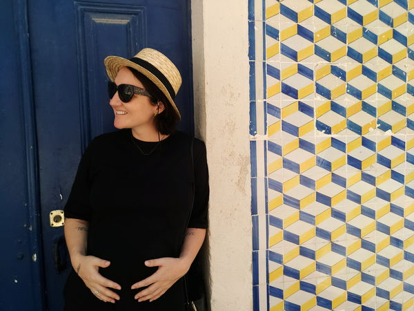 EyeEm Selects One Woman Only Only Women Standing Mid Adult Waist Up One Person Door Sunglasses Adult Adults Only Outdoors One Young Woman Only Day People Portrait Hands In Pockets Young Women Young Adult Building Exterior Smiling Tiles Tile Tiled Wall Blue