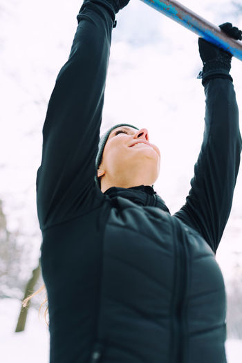 Female Athlete Exercising In Park In Winter With Snow Around The Park Athlete Exercise Lifestyle Nature Running Vertical Composition Winter Active Black Cold Female Fit Fitness Jogging Outdoors Outside Park Pull Ups Runner Snow Training White Workout