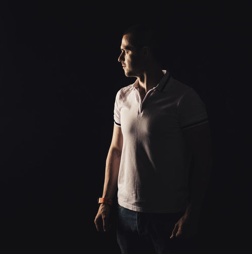 Man looking away against black background