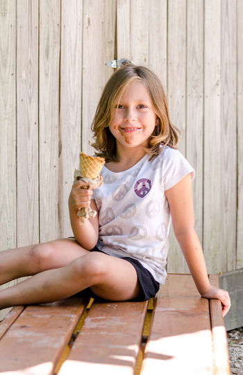Portrait of happy girl sitting on wood