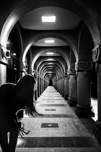 Silhouette Woman Standing In Illuminated Corridor Of Historic Building