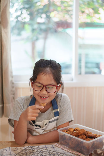 Smiling girl eating food at home