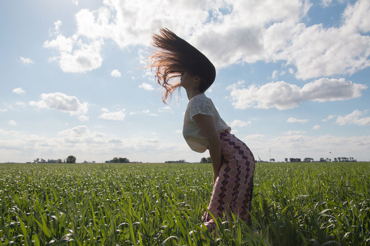 Portrait of beautiful woman shaking hair in green field