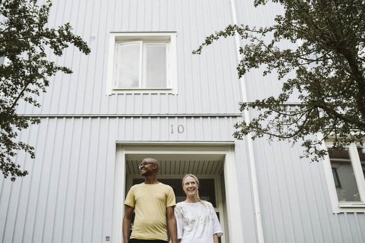 Low angle view of man and woman standing against building