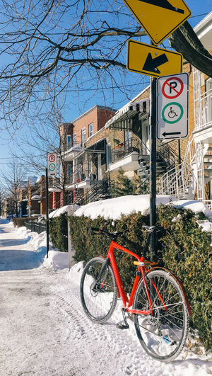 Bicycle on road by building during winter