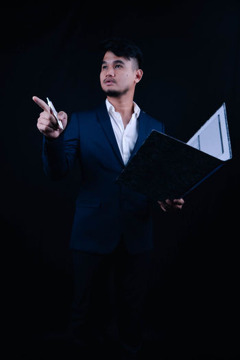 Young businessman holding file while standing against black background