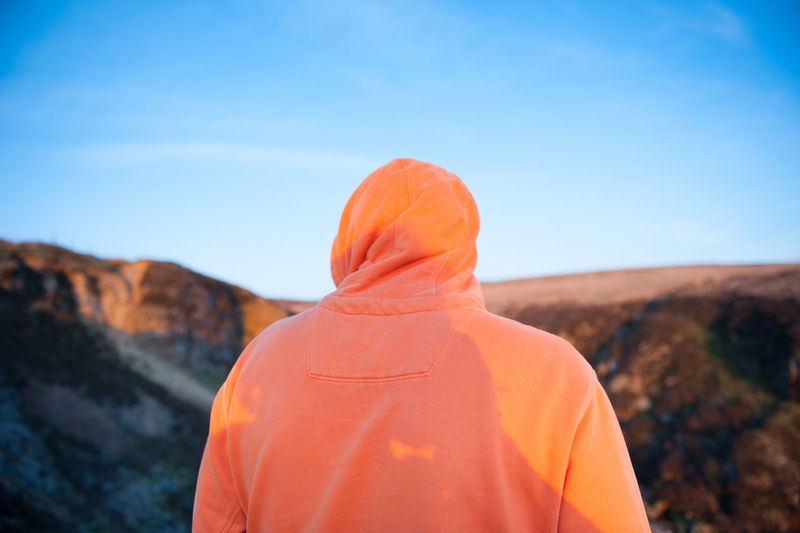 Arid Climate Beauty In Nature Close-up Day Focus On Foreground Hoodie Landscape Mountain Mountains Nature One Person Orange Orange Color Outdoors People Real People Rear View Scenics Sky Sky And Clouds Place Of Heart