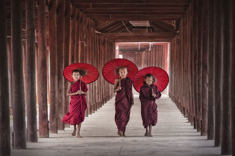 Monks with umbrellas walking in temple
