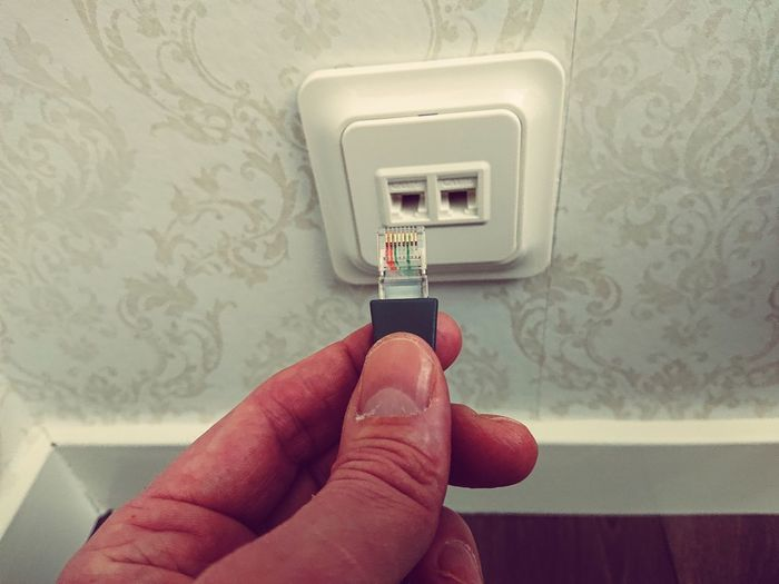 Close-up of hand holding network connection plug against wall