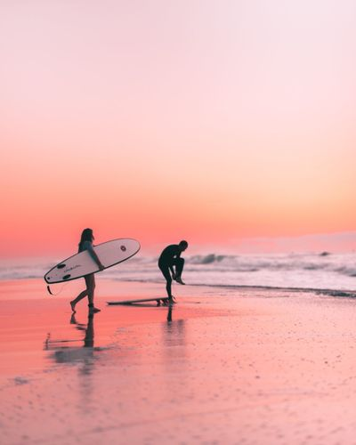 Silhouette man with surfboard on beach against sky during sunset