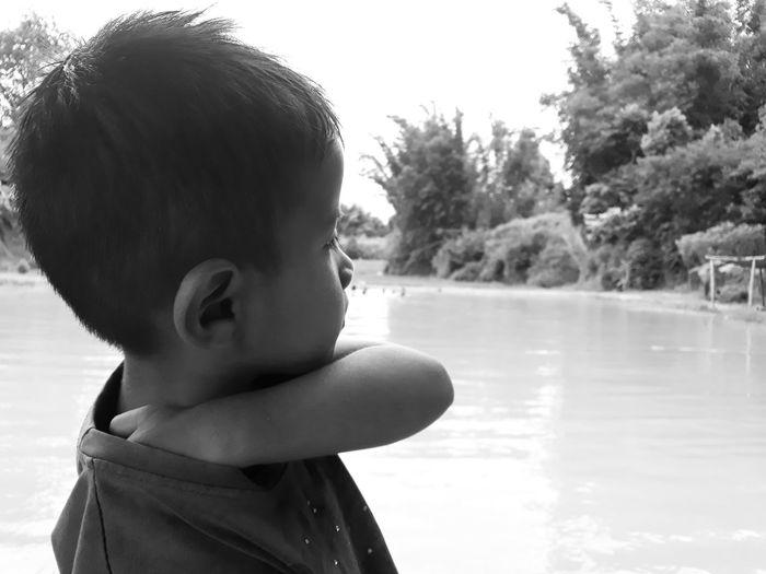 Cute boy looking away in lake
