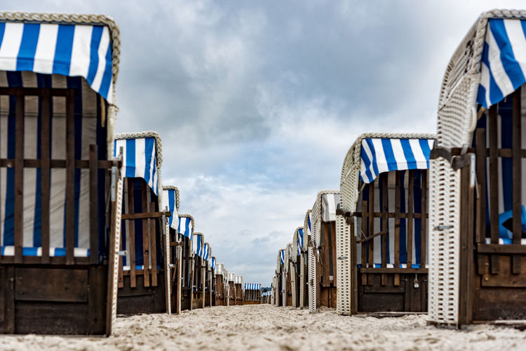 Hooded Beach Chairs In Row On Sand Against Cloudy Sky