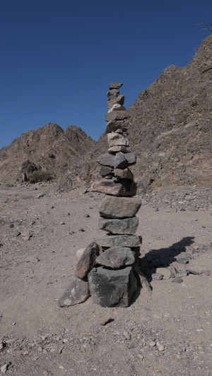 Stack of rocks on land against clear sky