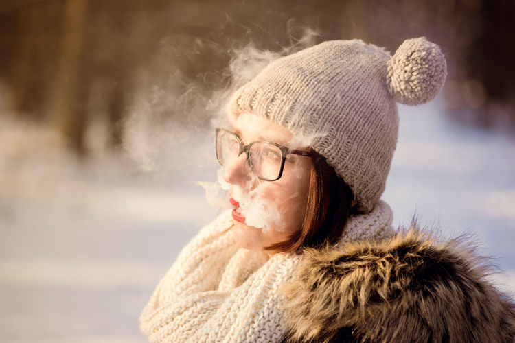 Close-Up Of Woman Wearing Warm Clothing While Smoking During Winter