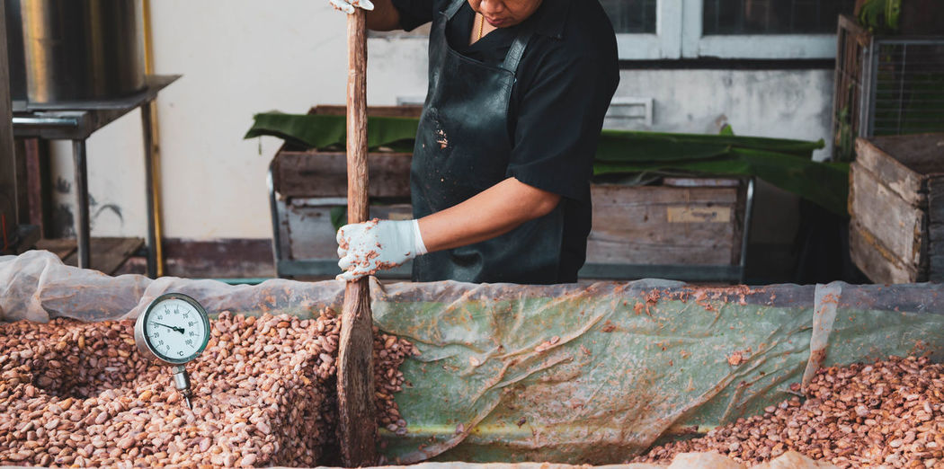 Midsection of man working with cocoa seeds at factory