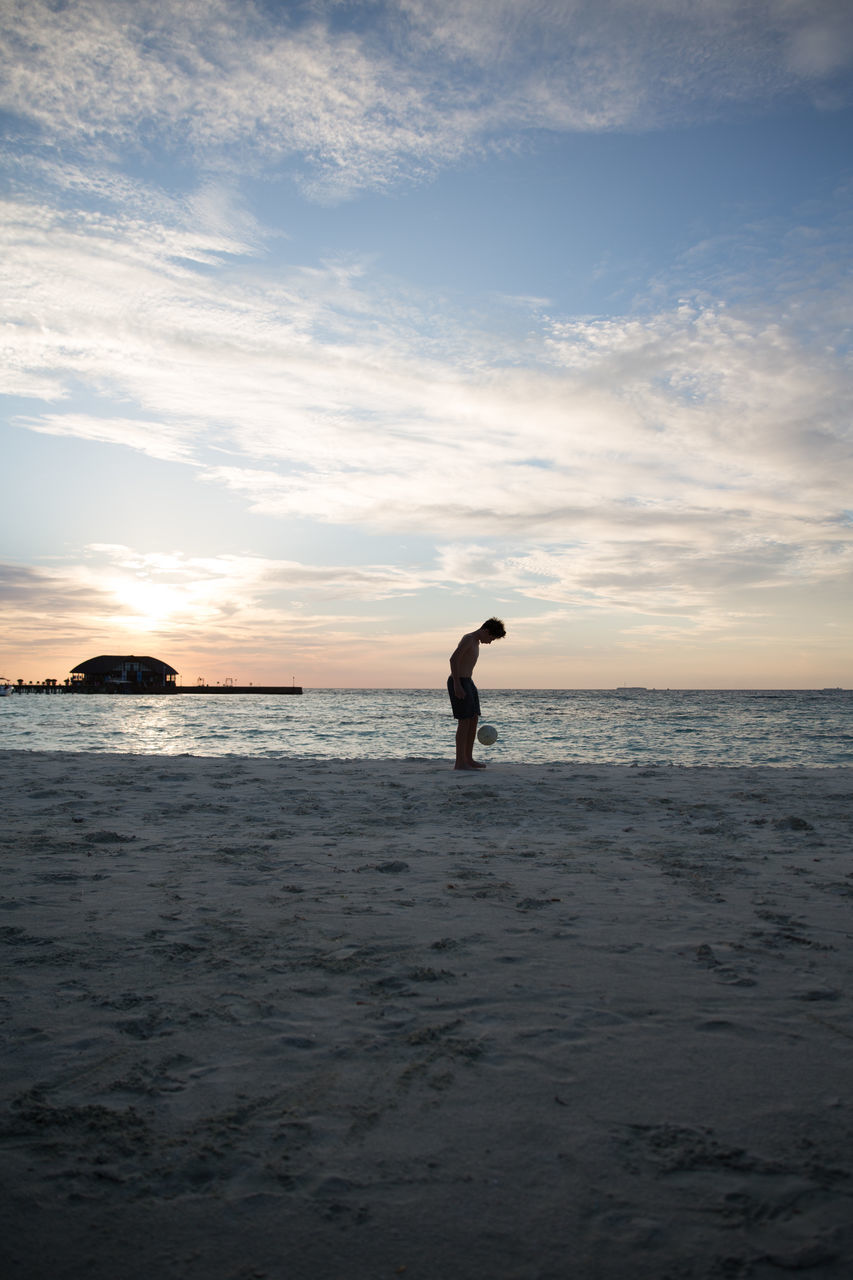 Shirtless Boy Playing Soccer At Beach Against Sky During Sunset