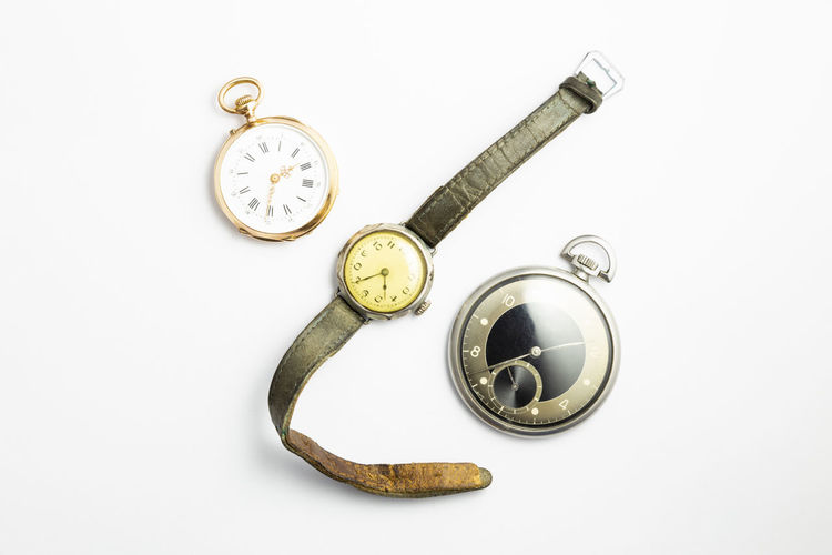 Directly above shot of pocket watches and wristwatch against white background