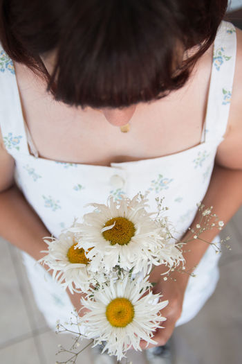 Midsection of woman holding white flowering plant