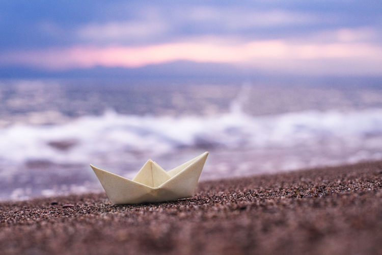 Close-up of paper ship floating on beach against sky during sunset