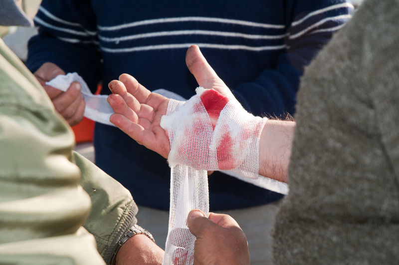Midsection of man wrapping bandage on hand