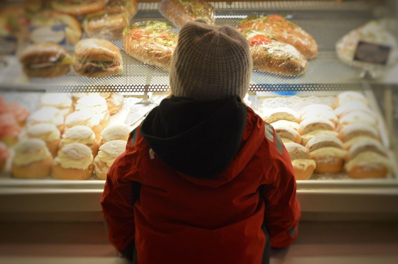 Rear view of girl looking towards food in display cabinet