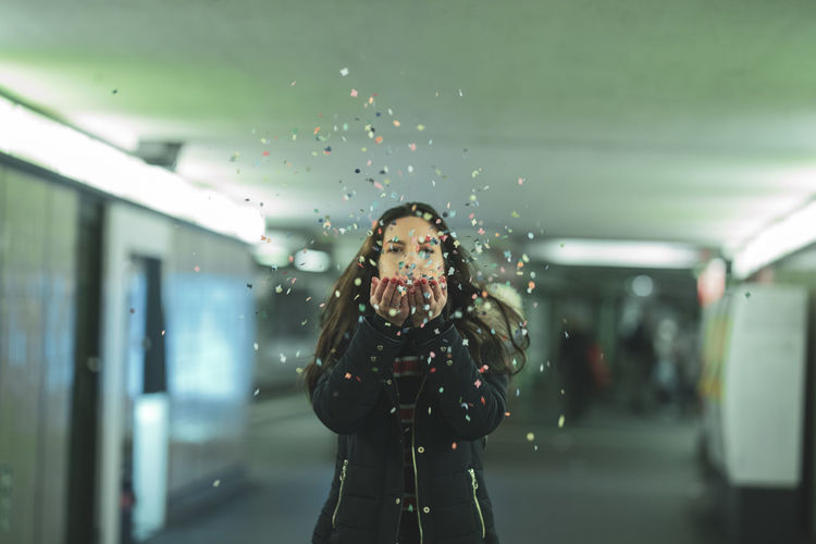 Portrait Of Woman Blowing Confetti At Subway Station