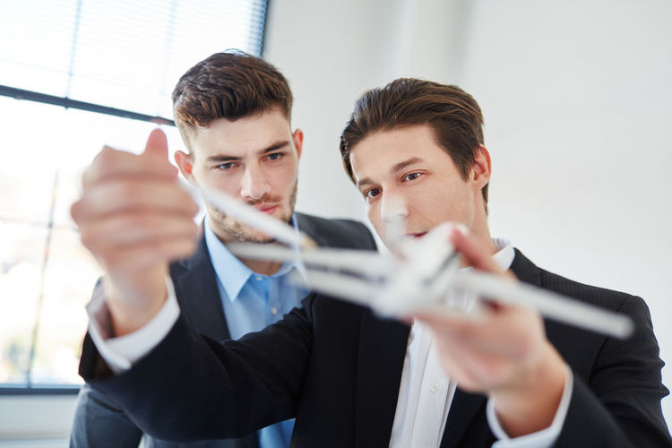 Businessman showing model airplane to colleague in office