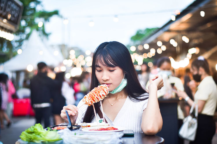 Portrait of woman eating food at restaurant