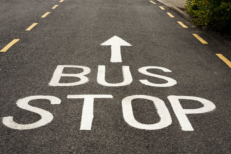 Bus Stop Sign and ahead Arrow painted in white on an asphalt road with yellow markings. Arrow Asphalt Public Transportation Road Road Markings Sign Transportation Ahead Ahead Arrow Bus Stop Direct Sign Parking Public Transport White White Paint Yellow Markings
