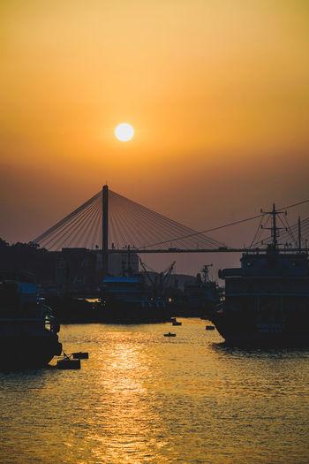 Silhouette bridge over sea against romantic sky at sunset