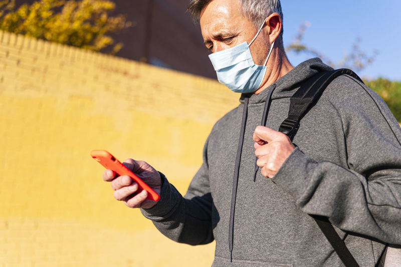 Midsection of man holding mobile phone standing outdoors