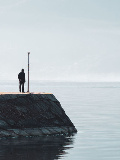 Rear View Of Person Standing By Sea Against Sky