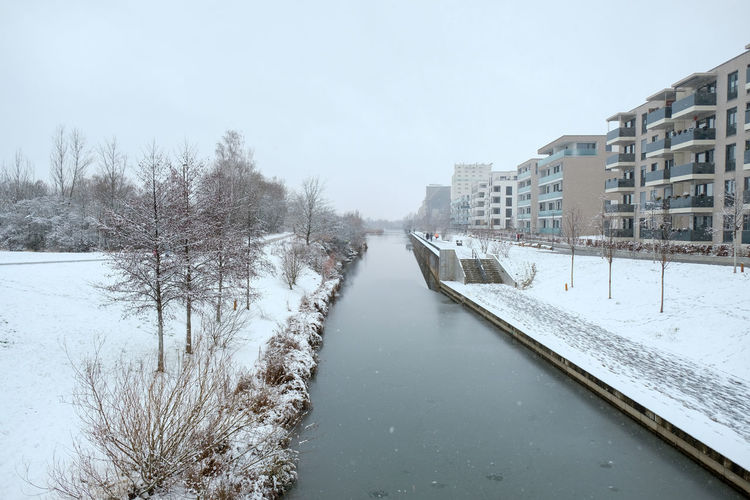 Frozen canal amidst buildings against sky during winter