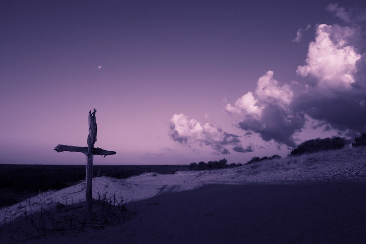 Cross on land against sky
