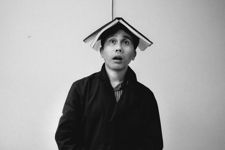 Man Balancing Book On Head While Standing By Wall