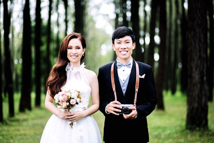 Portrait of happy wedding couple standing against trees in forest